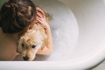 Boy taking a bath with golden retriever puppy dog