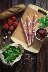 Overhead view of breadsticks wrapped in prosciutto on cutting board