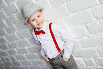 little boy wearing a red bow tie, suspenders and white shirtand against a white brick wall.