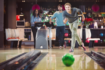 Smiling happy man is throwing the bowlingball