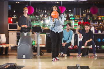 Cheerful young woman goes bowling with her friends