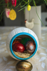 Multi-colored Easter eggs in a porcelain bowl in kitchen