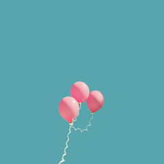 Three pink balloons against blue sky