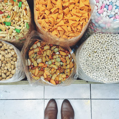 Feet standing in front of snacks in a market