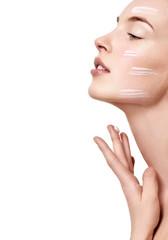 Beautiful Young Woman applying facial moisturizing cream.Skincar