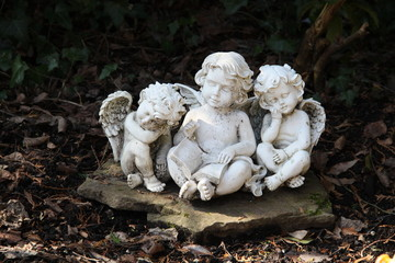 Drei Engel sitzen auf einem Grab