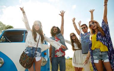 smiling hippie friends having fun over minivan car