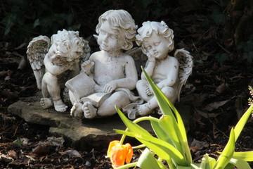 Drei Engel sitzen auf einm Grab neben Tulpe, die verwelkt ist