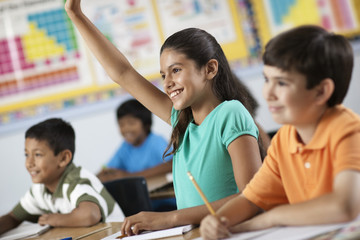 A group of young girls and boys in a classroom, classmates, A girl raising her hand,