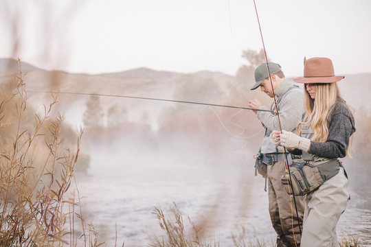 A couple fishing on a riverbank, tying the fly to the hooks for fly fishing,