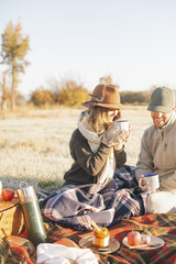 Two people, a couple on a winter picnic, seated on a tartan rug, holding hot drinks,