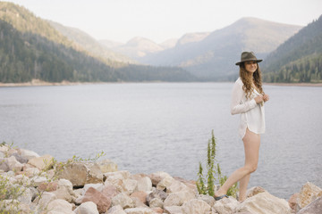 A woman in a hat and white shirt with a basket, by the shore of a mountain lake,