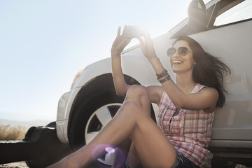 A woman seated in the shade of a car on the road, taking a photograph,