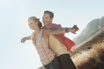 A couple standing close together, arms outstretched leaning into the breeze, in open country,