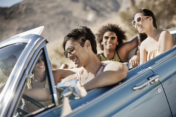 A group of friends in a pale blue convertible on the open road, driving across a dry flat plain surrounded by mountains,