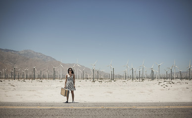 A young woman with a suitcase standing on the edge of the highway,