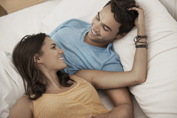 A young couple lying on a sofa gazing at each other, a man and woman, boyfriend and girlfriend,