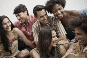 Six young people, three men and three women, laughing,