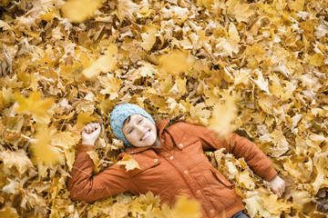 A woman lying on her back on the ground on a covering of autumn leaves,