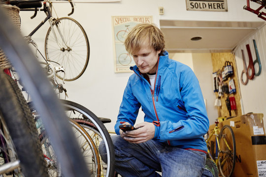 A young man using his smart phone in a cycle shop, making a call,