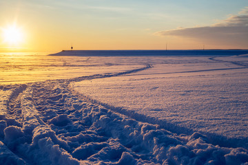 Cross country ski trace towards pier at sunset. Beautiful winter landscape.