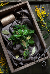 Fresh spring garni bouquet herbs seasoning bunch with scissors on vintage wooden table background. Thyme, rosemary, basil, parsley, pepper and bay leaves healthy spices. Rustic style, top view.