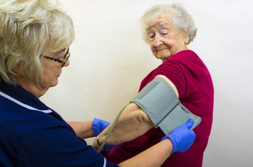 An elderly lady in her 90's with a nurse checking her blood pressure. Regular health checks are essential.