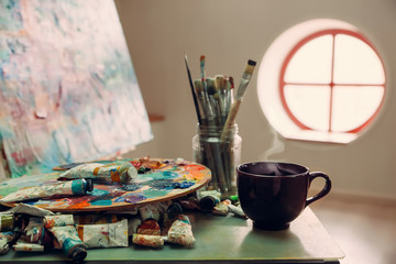 The workplace of the artist, brushes, paints, canvas on the easel. A mug with a hot drink. Selective focus, toned image.