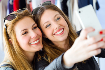 Two beautiful young women using their mobile phone in a clothes