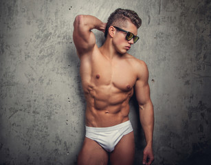 Shirtless muscular man in a white panties.