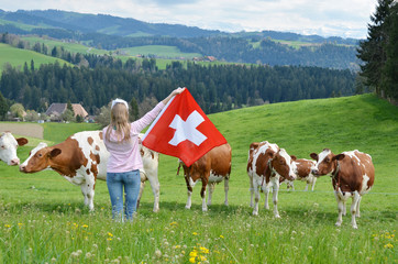 Wall Mural - Girl holding Swiss flag. Emmental, Switzerland