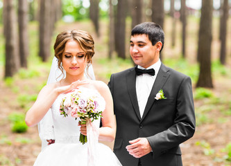 Groom and Bride in a park. Bridal wedding bouquet of flowers