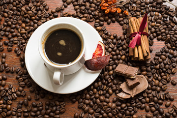 Coffee beans background with cofee cup, cinnamon, and chocolate