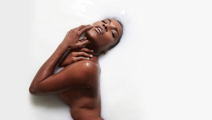 black woman in a milk bath treatment