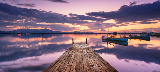 Perspective view of a wooden pier in the lagoon at sunset with fisherman boats, and a lot of reflections on the water.