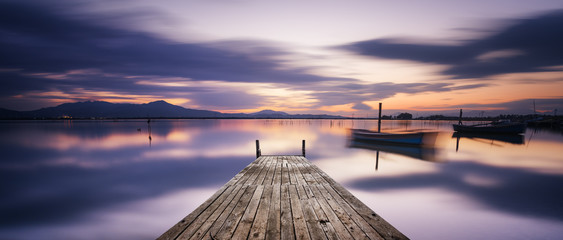 Perspective view of a wooden pier in the lagoon at sunset with perfectly calm water and reflection