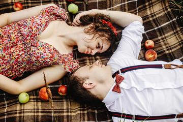 beautiful happy bride and stylish retro groom lying on tweed bla