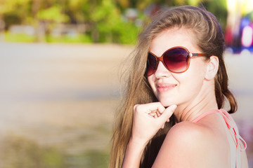young woman in sunglasses tanning on beach. portrait
