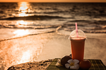 beautiful smoothie on the beach  at sunset.