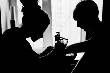 tattooing black and white, plugging sleeves, silhouetted against the window