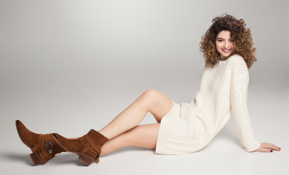 pretty girl in long white sweater and brown leather boots