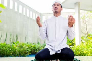Asian Muslim man praying at home