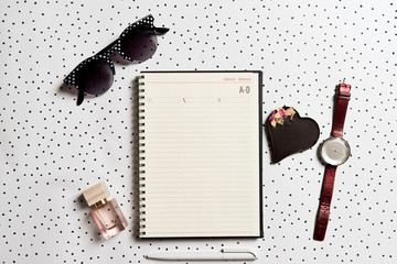An empty address book surrounded by romantic feminine objects