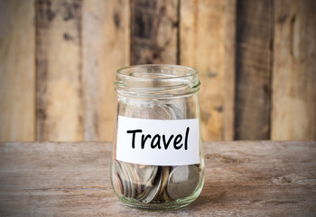 Coins in glass money jar with travel label, financial concept.