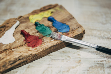 Painting brushes on wood with color