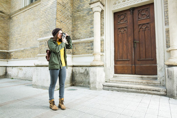Moder young woman takeing a pictures on a vacation. She is takeing a pictures of the architecture.