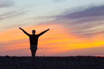 Silhouette of free woman enjoying freedom feeling happy at sunset. Serene relaxing woman in pure happiness and elated enjoyment with arms raised outstretched up.
