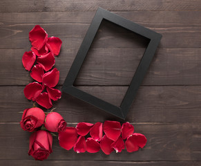 Red roses flowers and a frame picture are on the wooden backgrou