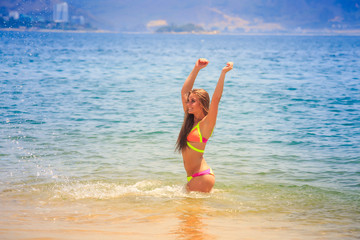 blonde slim gymnast in bikini squats smiles in azure sea