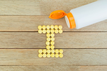 Yellow pills forming shape to I alphabet on wood background